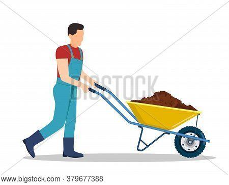 Man With Wheelbarrow Full Of Dirt Or Ground. Gardener Carries A Wheelbarrow With Organic Fertilizers