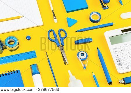 Assorted Office And School White And Blue Stationery And Calculator On Bright Yellow Background. Org