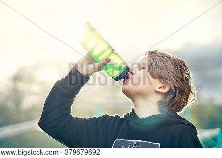 Side View Of Preteen Boy In Hoody Drinking Water From Plastic Bottle While Resting During Summer Act