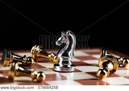 Silver Knight Chess Defeats Gold Pawns On Wooden Chessboard. Intellectual Duel And Tactical Battle I