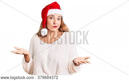 Beautiful young woman wearing christmas hat clueless and confused expression with arms and hands raised. doubt concept.