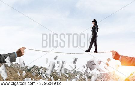 Businessman Walking Blindfolded On Rope Among Flying Documents And Above High Mountains As Symbol Of