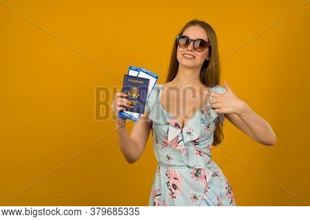 Joyful Young Woman In Blue Dress With Flowers And Sunglasses Pointing To Airline Tickets With A Pass