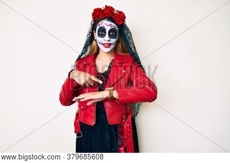 Woman wearing day of the dead costume over white in hurry pointing to watch time, impatience, upset and angry for deadline delay