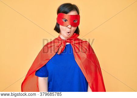 Brunette woman with down syndrome wearing super hero costume scared and amazed with open mouth for surprise, disbelief face