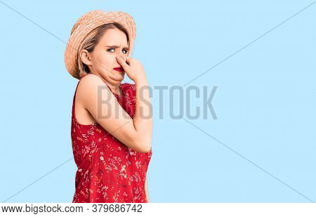 Young beautiful blonde woman wearing summer hat smelling something stinky and disgusting, intolerable smell, holding breath with fingers on nose. bad smell