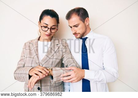 Beautiful couple wearing business clothes checking the time on wrist watch, relaxed and confident