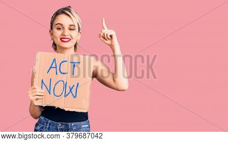 Young beautiful blonde woman holding act now banner surprised with an idea or question pointing finger with happy face, number one