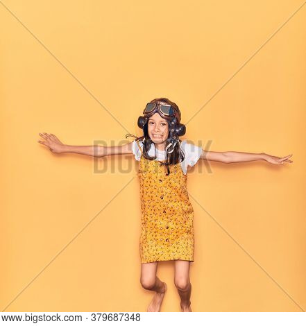 Adorable hispanic child girl wearing vintage aviator helmet and goggles smiling happy. Jumping with smile on face doing airplane gesture with arms open over isolated yellow background