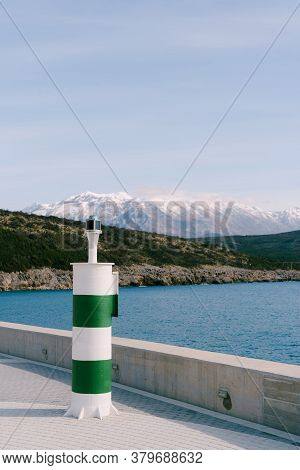 A Small Striped Green And White Lighthouse Against The Backdrop Of The Adriatic Sea And The Snow-cap
