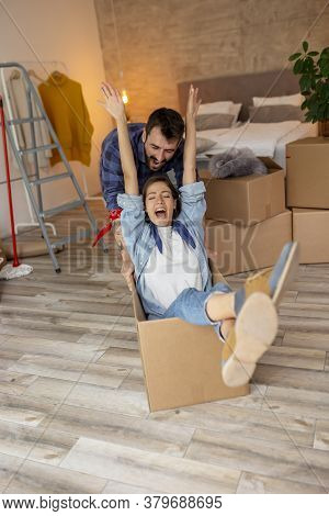 Couple In Love Moving In Together, Having Fun While Unpacking Cardboard Boxes With Their Belongings,
