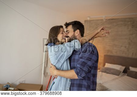 Beautiful Young Couple In Love Moving In Together, Hugging And Kissing In Their New Home