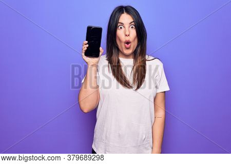 Young beautiful brunette woman holding smartphone showing screen over purple background scared and amazed with open mouth for surprise, disbelief face