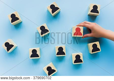 Partial View Of Hand Holding Wooden Block With Red Human Icon On Blue Background, Leadership Concept