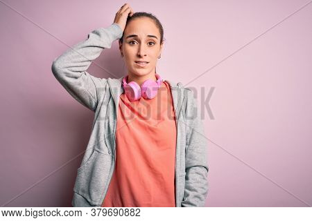 Beautiful sporty woman doing sport listening to music using headphones over pink background confuse and wonder about question. Uncertain with doubt, thinking with hand on head. Pensive concept.