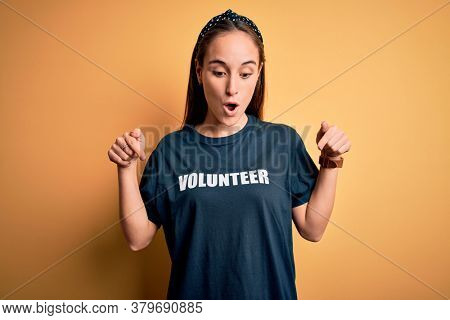 Young beautiful woman wearing volunteer t-shirt doing volunteering over yellow background Pointing down with fingers showing advertisement, surprised face and open mouth