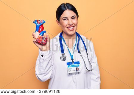 Young beautiful cardiologist woman wearing stethoscope holding heart over yellow background looking positive and happy standing and smiling with a confident smile showing teeth