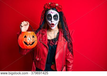 Woman wearing day of the dead costume holding pumpkin scared and amazed with open mouth for surprise, disbelief face