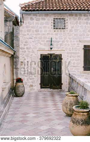 The Entrance To The House Is Closed Metal Door With A Grate Through The Yard With Large Pots For Flo