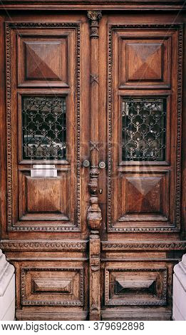 Brown Wooden Doors With Barred Windows And Carvings.