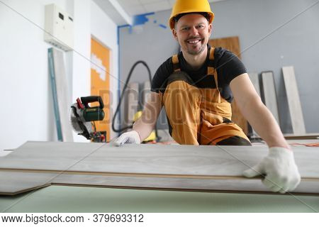 A Carpenter Smiles While Holding A Laminate. Laying Technology With Click Lock. Features Of Sawing L