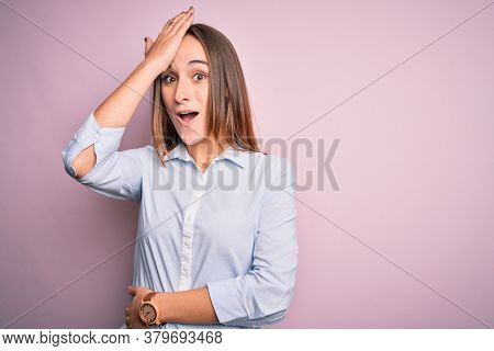 Young beautiful businesswoman wearing elegant shirt standing over isolated pink background surprised with hand on head for mistake, remember error. Forgot, bad memory concept.