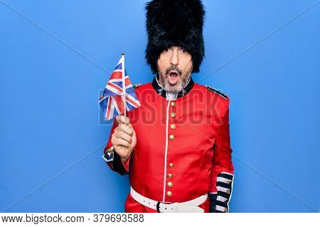 Middle age handsome wales guard man wearing traditional uniform holding united kingdom flag scared and amazed with open mouth for surprise, disbelief face