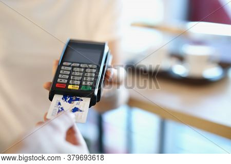 The Waiter Holds A Wireless Terminal To Pay The Bill. The Client In The Cafe Pays By Credit Card