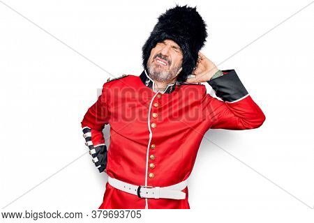 Middle age handsome wales guard man wearing traditional uniform over white background Suffering of neck ache injury, touching neck with hand, muscular pain