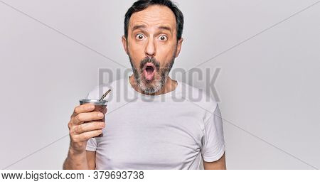Middle age handsome man drinking cup of mate tea over isolated white background scared and amazed with open mouth for surprise, disbelief face