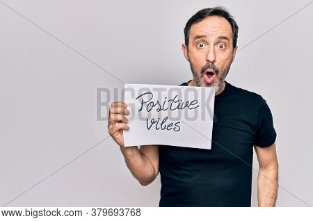 Middle age handosme man asking for good attitude holding paper with positive vibes message scared and amazed with open mouth for surprise, disbelief face