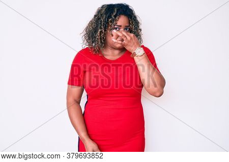 Young african american plus size woman wearing casual clothes smelling something stinky and disgusting, intolerable smell, holding breath with fingers on nose. bad smell