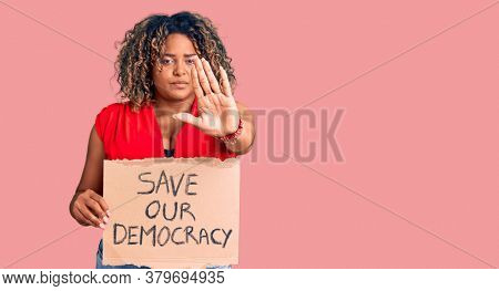 Young african american plus size woman holding save our democracy banner with open hand doing stop sign with serious and confident expression, defense gesture
