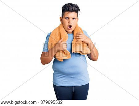 Little boy kid wearing sportswear and towel scared and amazed with open mouth for surprise, disbelief face