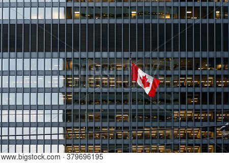 Canadian Flag In Front Of A Modern Office Building At Dusk Downtown Toronto, With Illuminated Office