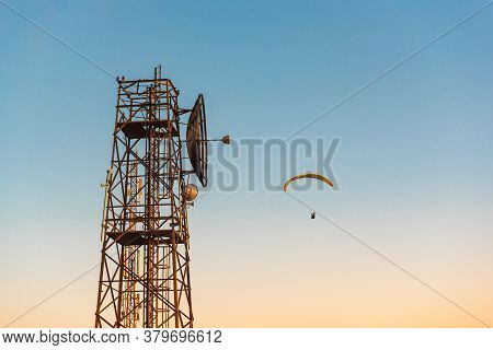 Telecommunications Mast And Flying Paraglider Over Menorca Island, Spain