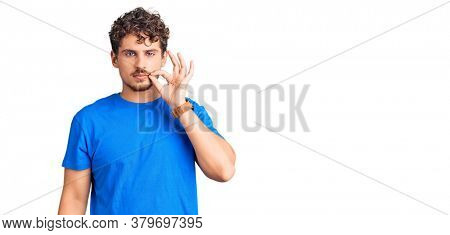 Young handsome man with curly hair wearing casual clothes mouth and lips shut as zip with fingers. secret and silent, taboo talking