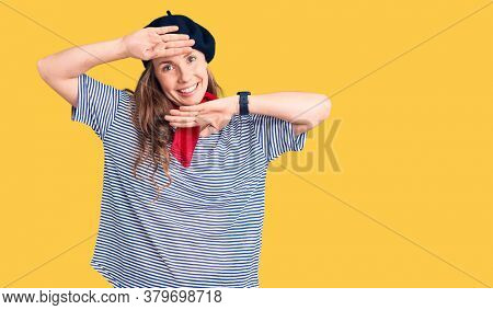 Young beautiful blonde woman wearing french beret and striped t-shirt smiling cheerful playing peek a boo with hands showing face. surprised and exited