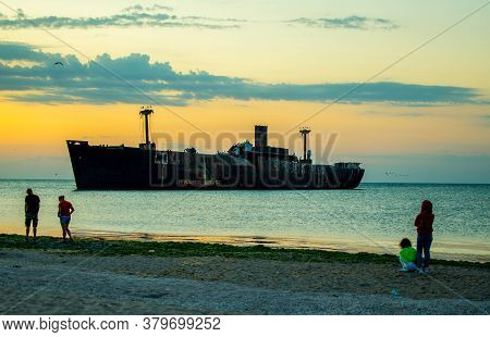 A Shipwreck. An Old Wreck Abandoned At Sea. Sunrise And People On The Beach.the Wreck Of The Ship
