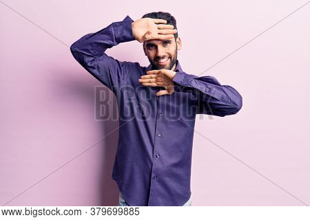 Young handsome man with beard wearing casual shirt smiling cheerful playing peek a boo with hands showing face. surprised and exited
