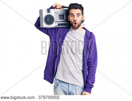 Young handsome man with beard listening to music using vintage boombox scared and amazed with open mouth for surprise, disbelief face