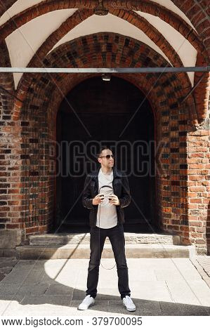 Smiling Man With Headphone In His Hand. Dj In Black Jaket With Black Glasses On Building Background