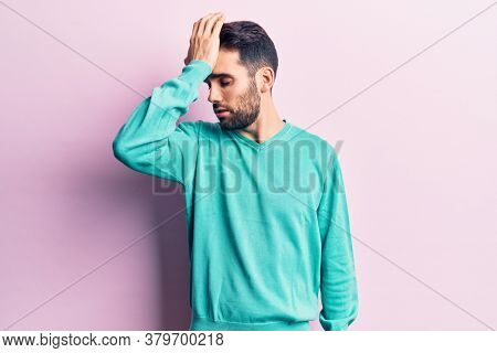 Young handsome man with beard wearing casual sweater surprised with hand on head for mistake, remember error. forgot, bad memory concept.