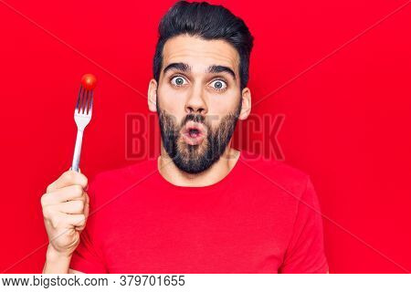 Young handsome man with beard holding fork with tomato scared and amazed with open mouth for surprise, disbelief face