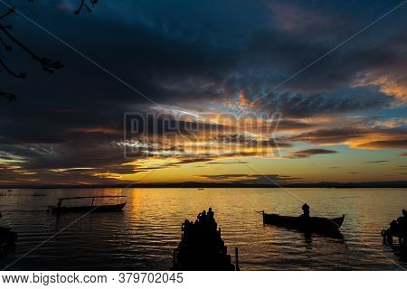 Silhouette Of Small Traditional Boats And Tourists At Dusk In The Albufera In Valencia, A Freshwater