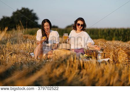 Best Friends Enjoying Their Time Together On A Picnic. Drinking Orange Juice And Smiling. Leisure An