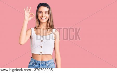 Young beautiful girl wearing casual sleeveless t shirt smiling positive doing ok sign with hand and fingers. successful expression.