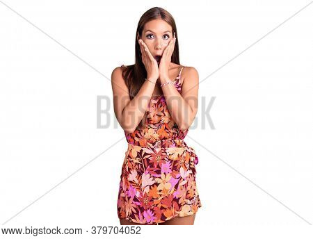 Young beautiful hispanic woman wearing casual clothes afraid and shocked, surprise and amazed expression with hands on face