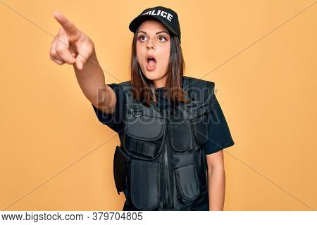Young beautiful brunette policewoman wearing police uniform bulletproof and cap Pointing with finger surprised ahead, open mouth amazed expression, something on the front