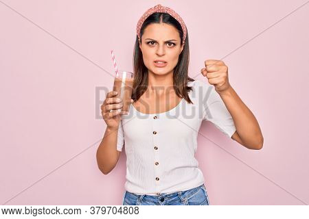 Young beautiful brunette woman drinking glass of chocolate beverage using straw annoyed and frustrated shouting with anger, yelling crazy with anger and hand raised